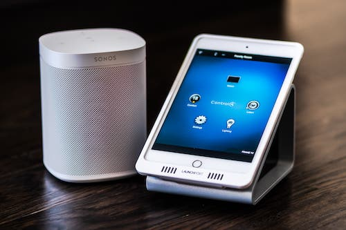 A smart phone sitting on a dock next to a Sonos speaker